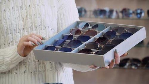 Organizer with Ten Pairs of Sunglasses in Women's Hands