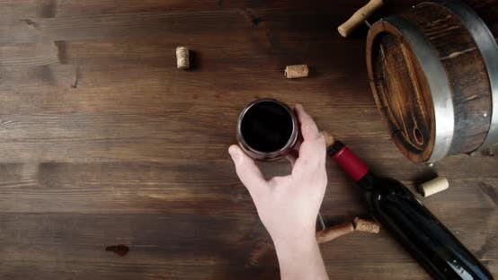 Thumbnail for A Man's Hand Puts a Glass of Wine on the Table