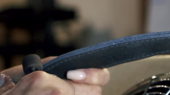 Young Leather Woman Worker Burnishing Edge of a Leather Belt During Manufacturing Process in His