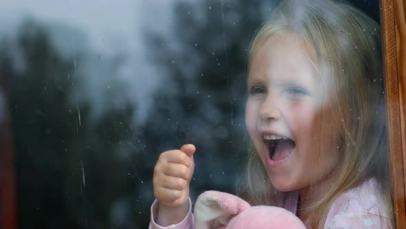Little girl crying by the window