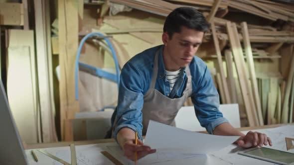 Artisan Looking at Blueprints