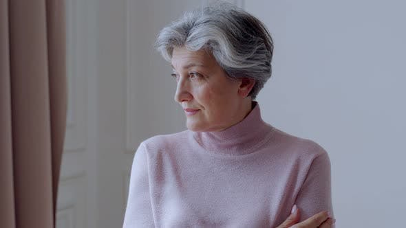 Thumbnail for Beautiful Old Woman with Gray Hair Smiles Standing at Home