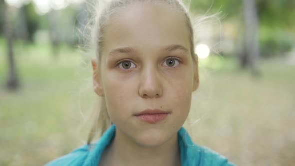 Cover Image for Portrait of a Young Irritated Blond Girl Looking at the Camera. Pretty Caucasian Teen Standing in