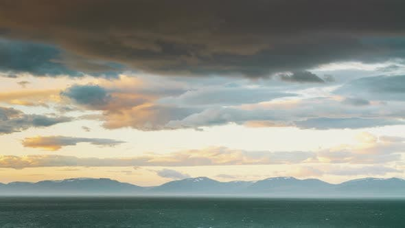 Thumbnail for Rolling Moving Clouds In Sunset Light Over Nothern Snow Mountains And Arctic Sea Waves In Iceland