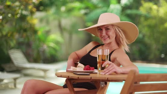 Thumbnail for Woman smiling by the pool at the resort