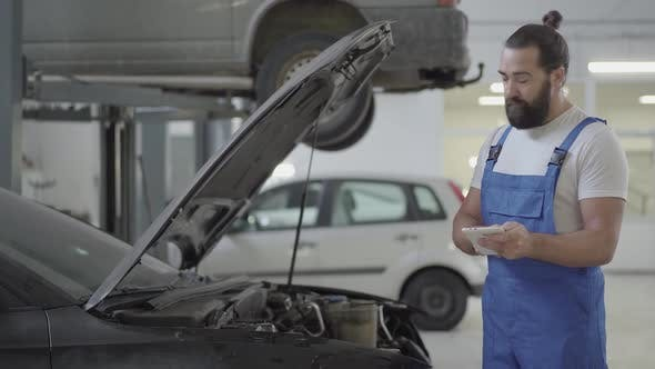 Thumbnail for Adult Mechanic Standing Near the Car with an Open Hood and Verifies Information on His Phone