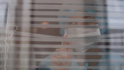 Nurse looking through window of hospital with disturbed look, coronavirus