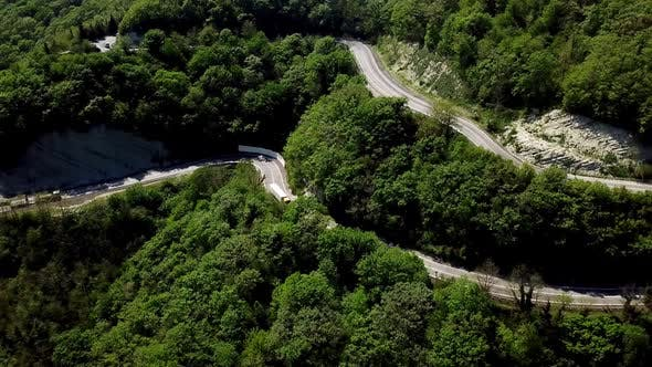 Thumbnail for Aerial POV Truck at Mountain Road Going Through Forest Landscape,