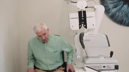 Senior Man Doing Eye Vision Test On Modern Equipment