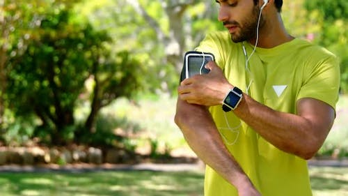 Jogger man touching the mp3 player in armband 4k