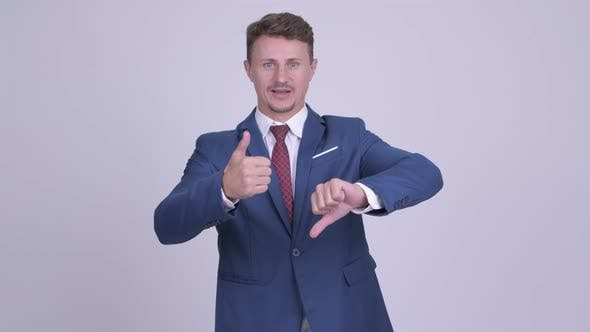 Thumbnail for Handsome Bearded Businessman Choosing Between Thumbs Up and Thumbs Down