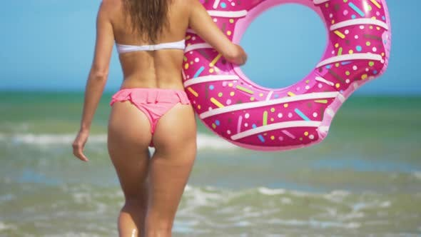 Thumbnail for Young Woman Buttocks Walking To the Sea with Pink Inflatable Donut