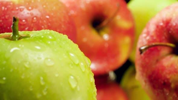Thumbnail for Makro-Video der Kamera bewegt sich zwischen frischen reifen grünen nad roten Äpfeln bedeckt mit Wassertröpfchen oder