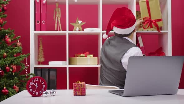Thumbnail for Santa Claus Assistant in Office Concept. Cheerful 40s Man Has Fun Sorting Gifts