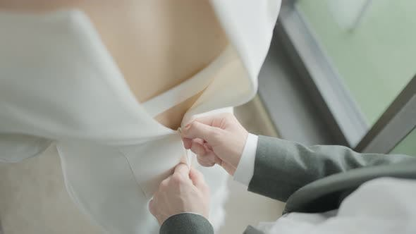 Husband buttoning dress on bride