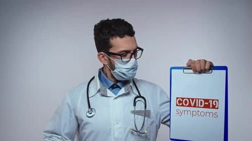 Male Doctor is Holding a Picture with the Inscription COVID 19 Symptoms Coronavirus Epidemic