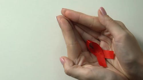 Red Ribbon in Female Hands Care of HIV Patients