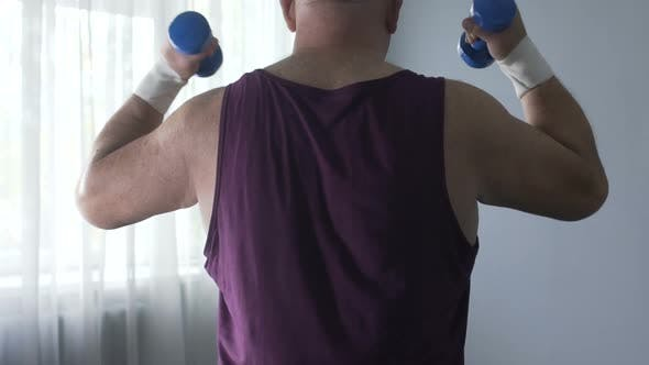 Cover Image for Man Doing Sports Slowly Lifting Dumbbells in His Ward, Recovering from Injury