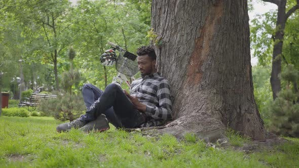 Thumbnail for Handsome African American Man Sitting Near His Bicycle Under an Old Tree in the Park Reading a Book