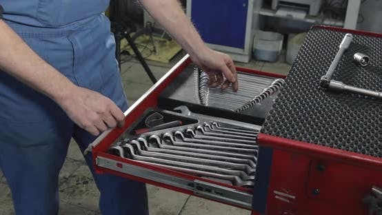 Auto Mechanic Opens A Box With Working Tools For Repair And Diagnostics Of Cars