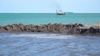A Boat Does Sand Dredging on the Beach