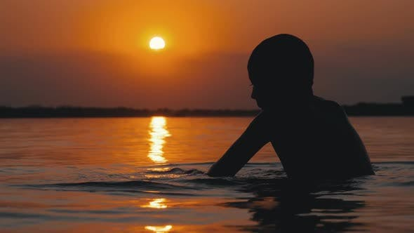 Cover Image for Silhouette of Boy Sitting in the Water on Background of Sunset and Orange Path. Slow Motion