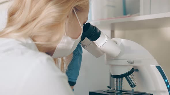 Thumbnail for Scientist Microbiologist Examines Biological Blood Samples Under a Microscope. Female Researcher