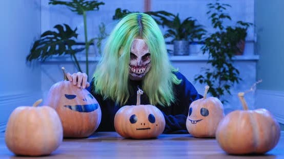 Thumbnail for Halloween Day. Young Woman in Horrible Mask with Pumpkins