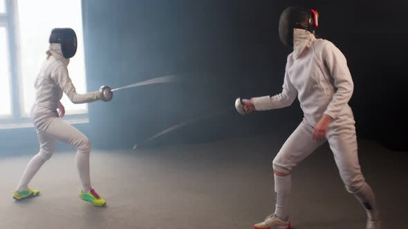 Thumbnail for Two Young Women Having an Intense Training in a Fencing Duel in the Dark Smoky Studio