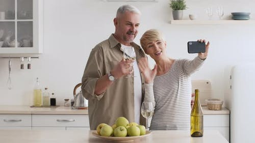 Mature Couple Making Video Call Via Smartphone In Modern Kitchen