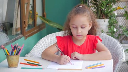 Cute Small Little Girl Artist Playing Alone Drawing Coloring Picture with at Home Relaxing Sits in