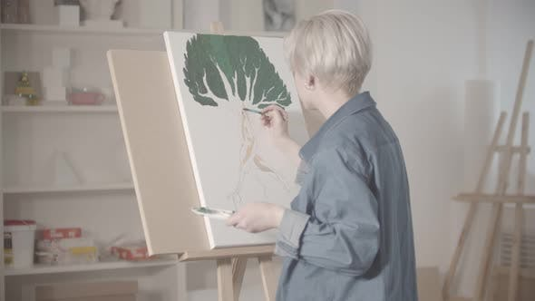 Thumbnail for A Young Blonde Woman Draws a Tree with Paints