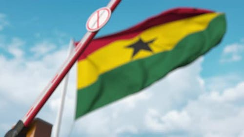 Closing Barrier with STOP CORONAVIRUS Sign at Flag of Ghana