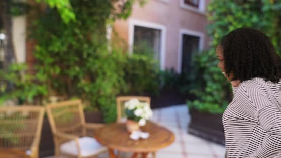 Thumbnail for Happy black female on the phone with boyfriend, walking around charming patio