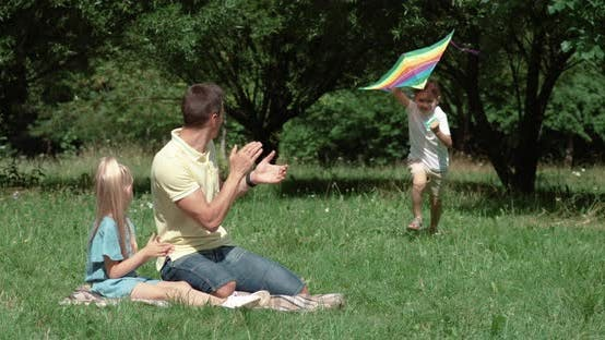 Family Day, Picnic in Nature, Boy Run Through a Clearing and Play with a Kite, Father and Daughter