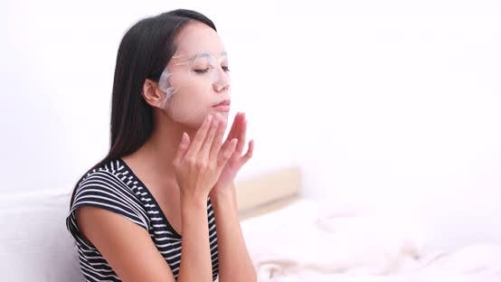 Thumbnail for Woman apply paper mask on her face