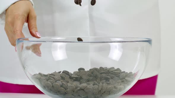 Thumbnail for Closeup Chocolatier Pours Dark Chocolate Chips on White Background, Slow Motion