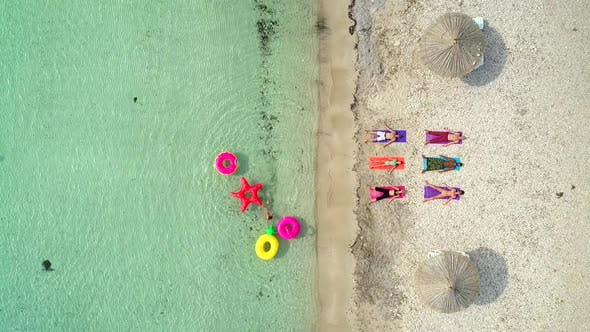 Aerial view of people lying in yoga pose on on the with inflatables.