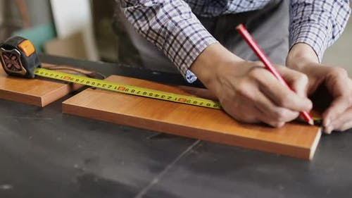 Male Hands Using a Yellow Tape Measure To Measure a Piece of Wood