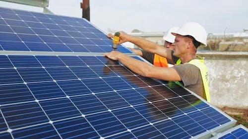 Technician installing solar cell. Technicians mounting photovoltaic solar panels