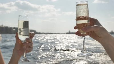 Ladies Hands Hold Glasses with Champagne Against River