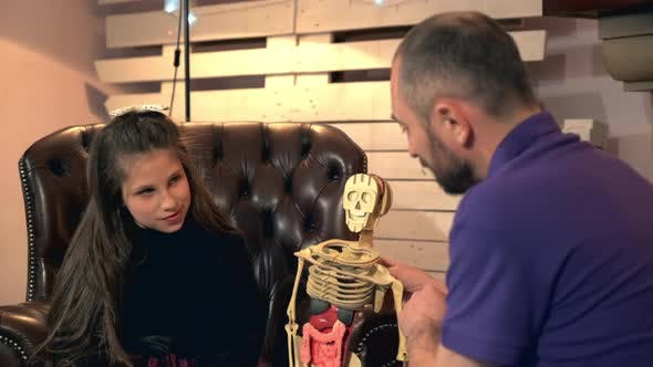 Father Explaining His Younger Daughter the Bone Structure of Human Body Showing on Skeleton