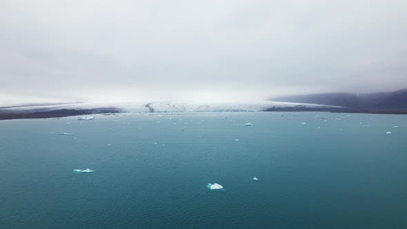 Icebergs Scattered in the Ocean With the View of the Mountains on Clear Sky