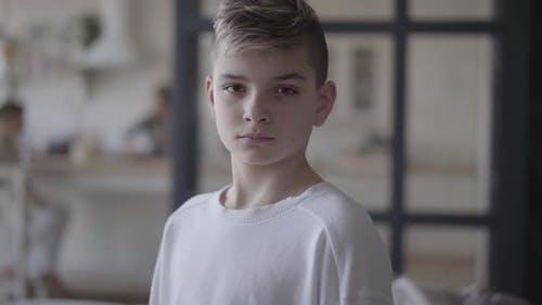 Porträt eines jungen Jungen Blick in die Kamera. Der emotionlose Junge in einem weißen T-shirt