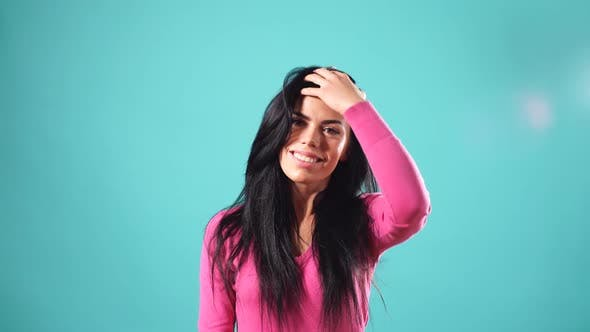 Thumbnail for Smiling Brunette Woman Playing with Her Hair and Looking at the Camera Over Turquoise Background.