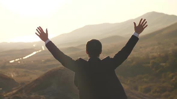 Businessman Rises Hands on Nature