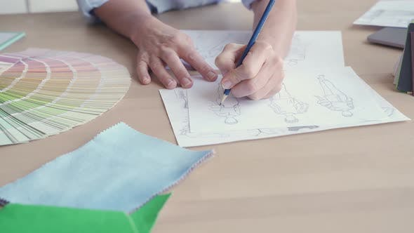 Female Fashion Designer Drawing Sketches on Table Close Up View