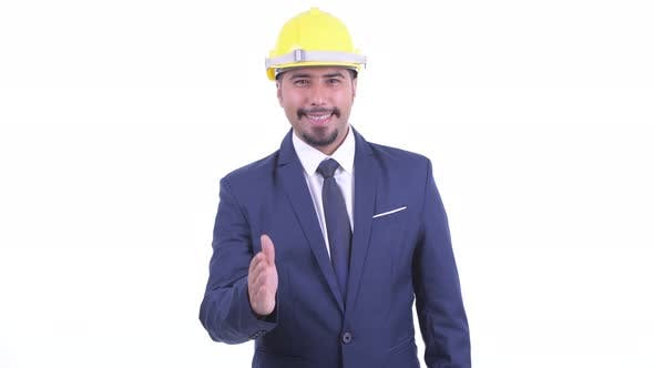 Thumbnail for Happy Bearded Persian Businessman As Engineer Giving Handshake