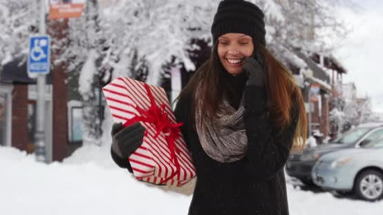 Thumbnail for Girl talking on cellphone while holding Christmas gift on snowy street downtown