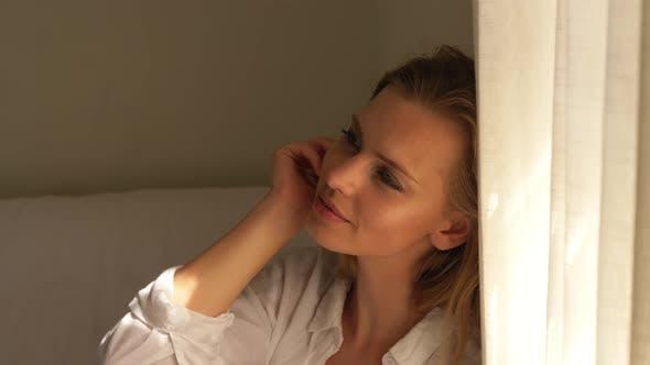 blonde weiblich sitzen in weiß Schlafzimmer lächelnd durch die Vorhang